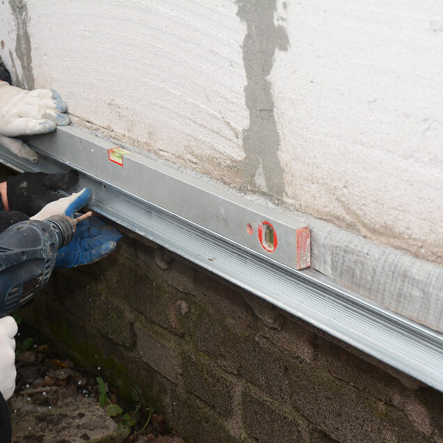 old house foundation wall repair and renovation with installing metal sheets for waterproofing and protect from rain
